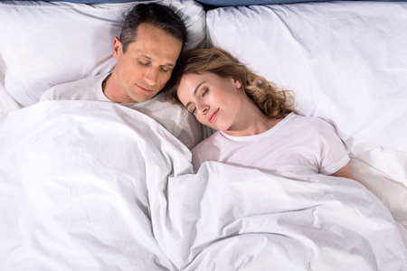 Photo for overhead view of couple sleeping in bed at home - Royalty Free Image