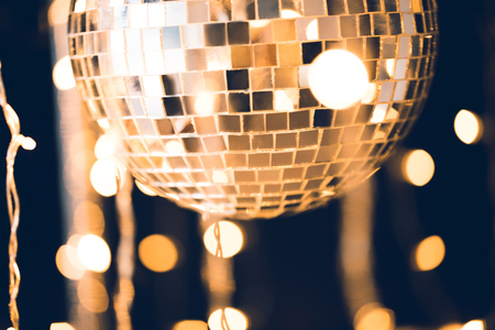 Photo pour close-up shot of glossy disco ball on black background with garland hanging around - image libre de droit