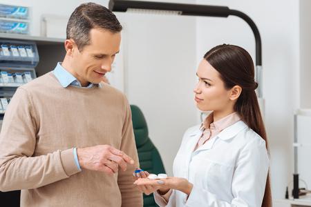 Foto de portrait of ophthalmologist show contact lens to patient in clinic - Imagen libre de derechos