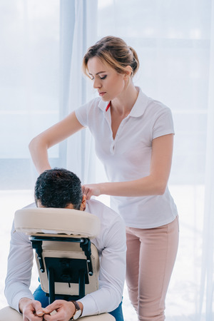 Foto de attractive masseuse doing shoulders massage on seat at office - Imagen libre de derechos