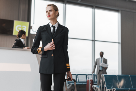 Photo pour female pilot with suitcase at airport reception - image libre de droit