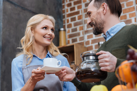 Photo pour husband proposing coffee to wife in kitchen - image libre de droit