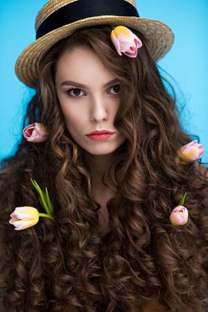 Foto de serious woman in canotier hat with flowers in her long curly hair looking at camera - Imagen libre de derechos