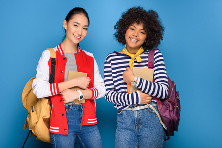 Photo for happy female african american and asian students posing with books, isolated on blue - Royalty Free Image