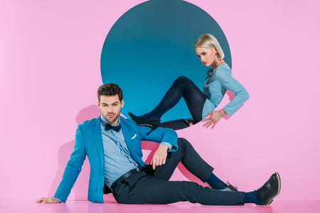 Foto per attractive stylish couple sitting and looking at camera on pink - Immagine Royalty Free
