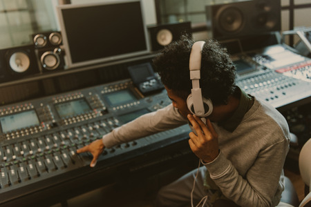 Photo pour young african american sound producer working with analog equalizer at studio - image libre de droit