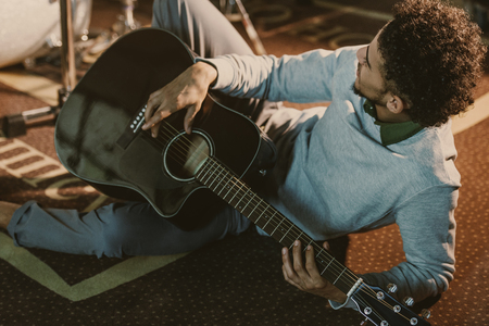 Photo for handsome african american man lying on floor of studio with acoustic guitar - Royalty Free Image