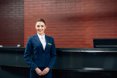 Photo pour young beautiful hotel receptionist standing in front of workplace - image libre de droit