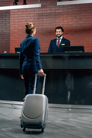 Photo pour businesswoman with luggage going at hotel reception counter - image libre de droit