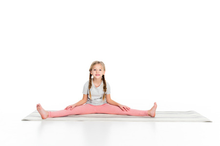 Foto de adorable child stretching on yoga mat isolated on white - Imagen libre de derechos