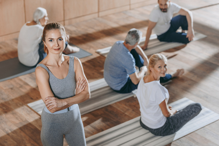 Photo for high angle view of female instructor looking at camera while senior people exercising on yoga mats - Royalty Free Image
