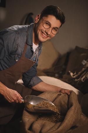 Foto de smiling worker in apron pouring coffee beans into sack bag - Imagen libre de derechos