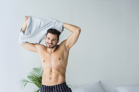 Photo pour handsome sexy smiling man taking off his t-shirt in bedroom - image libre de droit