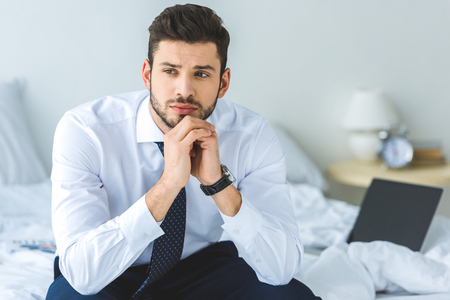 Foto de handsome thoughtful businessman in white shirt and tie sitting on bed - Imagen libre de derechos