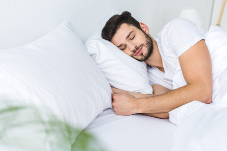 Foto per bearded man sleeping on bed in bedroom - Immagine Royalty Free