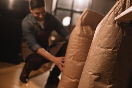 Foto de partial view of worker in apron with paper bags of coffee beans - Imagen libre de derechos