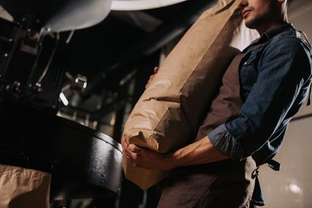 Foto de partial view of worker in apron holding paper bag of coffee beans in hands - Imagen libre de derechos