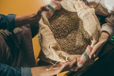 Foto de cropped shot of workers holding sack bag with coffee beans together - Imagen libre de derechos