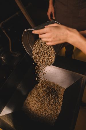 Foto de partial view of coffee roaster pouring coffee beans into roasting machine - Imagen libre de derechos