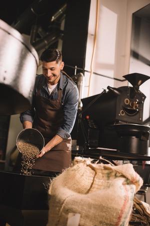Foto de coffee roaster pouring coffee beans into roasting machine - Imagen libre de derechos