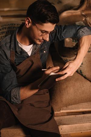 Foto de portrait of coffee roaster in eyeglasses and apron making notes in notebook - Imagen libre de derechos