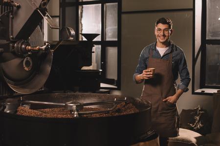 Foto de smiling coffee roster with cup of coffee having break during work - Imagen libre de derechos