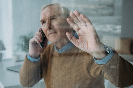 Photo pour Behind the glass view of senior man making a phone call - image libre de droit