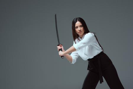 Photo pour young asian woman fighting with katana sword and looking at camera isolated on grey - image libre de droit
