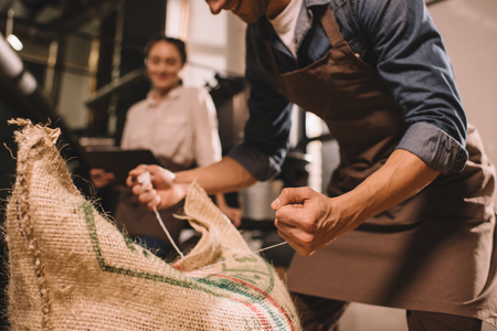 Foto de partial view of worker tying sack bag with coffee beans - Imagen libre de derechos