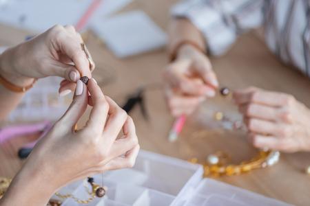 Photo pour cropped shot of women making accessories of beads at workshop - image libre de droit