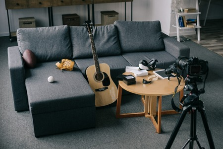 Photo for acoustic guitar and cameras with gray sofa in empty room - Royalty Free Image