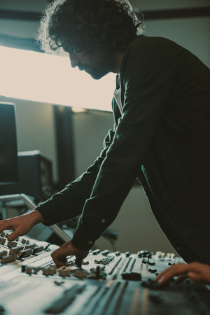 Photo for handsome young sound producer working with recording equipment - Royalty Free Image