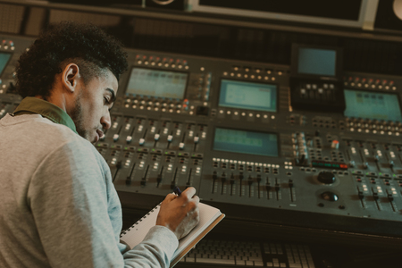Photo for handsome young musician writing in notebook at recording studio - Royalty Free Image