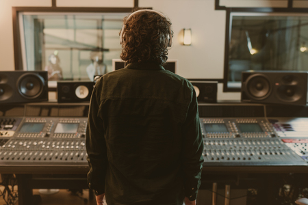 Photo pour back view of sound producer in headphones at studio - image libre de droit