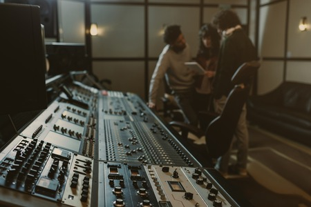 Photo for blurred group of musicians spending time at recording studio with graphic equalizer - Royalty Free Image