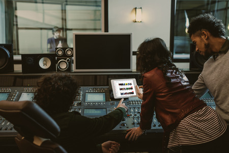 Photo for sound producers using tablet together at recording studio with youtube website on screen - Royalty Free Image