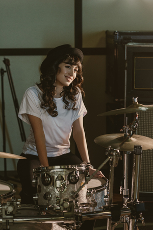 Photo for attractive female drummer sitting at drum set - Royalty Free Image