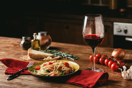 Foto de traditional italian pasta with tomatoes and arugula in plate and glass of red wine - Imagen libre de derechos
