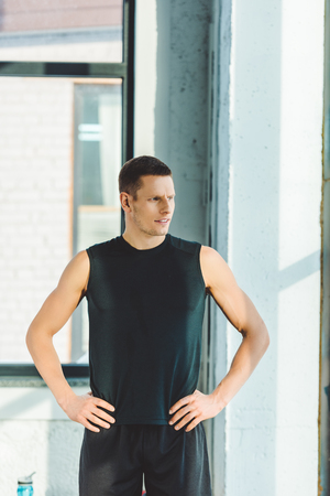 Photo pour portrait of young sportsman akimbo in sportswear standing in gym - image libre de droit