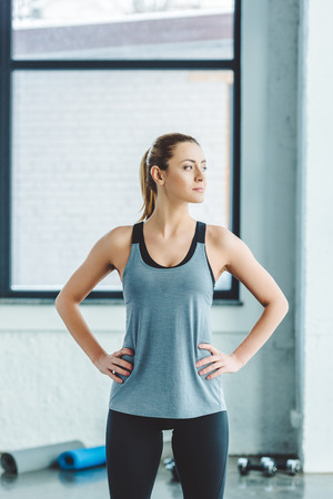 Photo pour portrait of young caucasian woman akimbo in sportswear in gym - image libre de droit