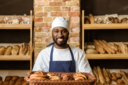 Photo pour smiling african american baker holding basket with sweet pastry - image libre de droit
