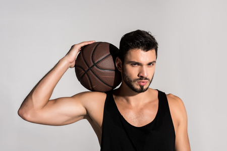 Photo pour handsome young basketball player with ball isolated on grey - image libre de droit