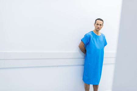 Photo for male patient in medical gown standing at wall in hospital - Royalty Free Image