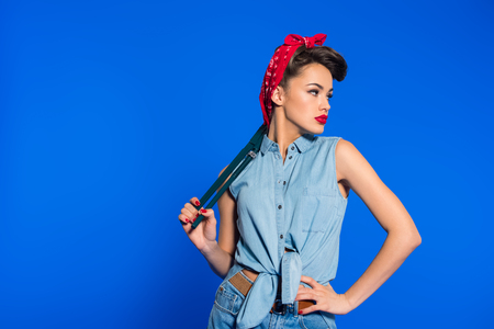 Photo pour fashionable young woman in pin up style clothing with wrench isolated on blue - image libre de droit