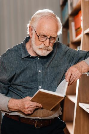 Photo pour grey hair librarian reading book - image libre de droit
