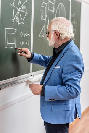 Photo pour grey hair professor correcting something at blackboard - image libre de droit