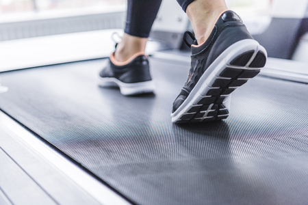 Foto de cropped shot of woman in jogging sneakers running on treadmill - Imagen libre de derechos
