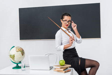 Photo for young sexy teacher in stockings with pointer sitting on desk in front of chalkboard - Royalty Free Image