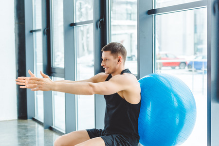 Photo pour side view of smiling sportsman exercising with fitness ball in gym - image libre de droit
