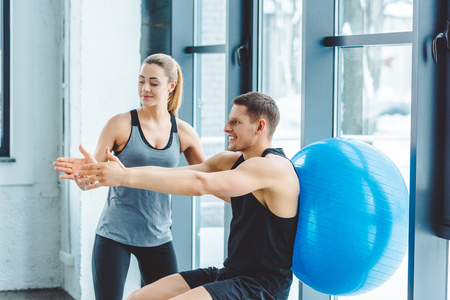 Foto de woman helping smiling man exercising with fitness ball in gym - Imagen libre de derechos